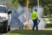 Smoke rises out of a manhole near 13th and Delaware Streets as city crew member Mark Hegeman, left, and Matt Fishburn prepare to test another sewer line area. City crews were smoke testing sewer lines Thursday.