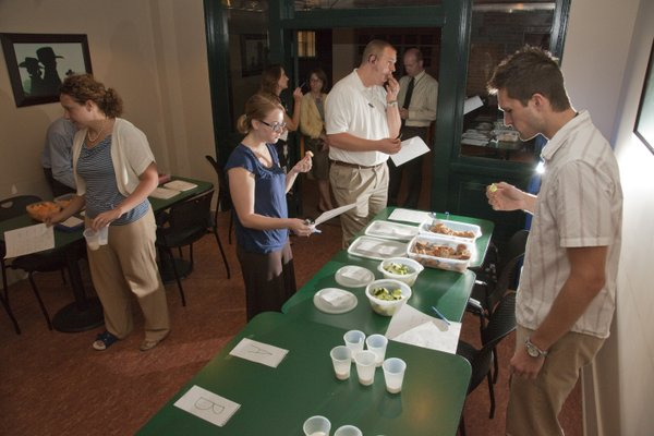 The World Company employees and visitors taste test local versus nonlocal foods in the basement of The News Center. From left, in the foreground, are Christine Metz, Amy Elzea, Charles Clark and Nick Nelson.