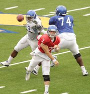 Kansas quarterback Jordan Webb throws as offensive lineman Jeff Spikes (74) fends off the rush by defensive end Toben Opurum (35) during a scrimmage on Saturday, Aug. 20, 2011 at Memorial Stadium.