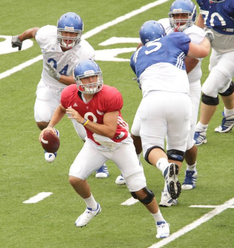 Quarterback Quinn Mecham looks to avoid the defensive rush during a scrimmage on Saturday, Aug. 20, 2011 at Memorial Stadium.