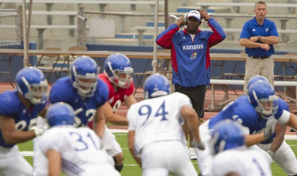 Kansas head coach Turner Gill adjusts his headset as he watches over the team's scrimmage on Saturday, Aug. 20, 2011 at Memorial Stadium.