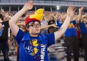 Wichita freshman Nicholas Beddow learns how wave the wheat with his fellow incoming freshmen during the annual Traditions Night at Memorial Stadium. The annual event teaches new Jayhawks various traditions such as the rock chalk chant, waving the wheat and how to clap to the school fight song.