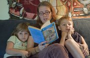 "Lawrence mom and kids&squot; fiction lover Abby Hess, center, reads ""Iggie&squot;s House"" by Judy Blume, to her children Nene, 4, left and Danny, 6, right. Hess says she loves reading young adult and childrens&squot; books just as much as she does adult fiction and nonfiction."