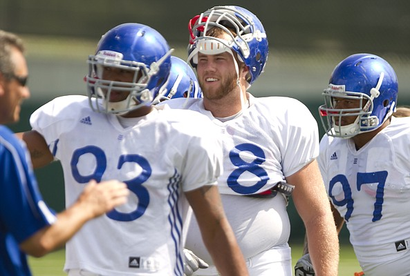 Kansas defensive tackle Shane Smith, second from right, takes instruction with the defensive line during practice on Tuesday, Aug. 23, 2011.