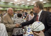 After being presented a signed 2010-2011 KU men's basketball, David Booth, chairman and CEO of Dimensional Fund Advisors, shakes hands with Jack Arensberg. Booth's first job was working for Jack at Arensbergs shoes. Booth, a 1964 LHS graduate and owner of the original rules of basketball, was the keynote speaker at the event.