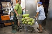 Jeremy Farmer, left, and and Ace Hickey push a load of watermelons from the fields at Leavenworth Federal prison that volunteers working with the Therapy and Mentoring Horticulture Program delivered to Just Foods. Around 500 pounds of produce were delivered to the food warehouse in Lawrence on Thursday, August 25, 2011.
