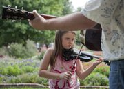 Riley Shaw, 7, practices with her father John Shaw, Lincoln, Neb., at the 31st Kansas State Fiddling and Picking Championships in South Park on Sunday, August 28, 2011. Riley competed in the youth fiddle competition and her dad competed in the open fiddle and flat-pick guitar contests.