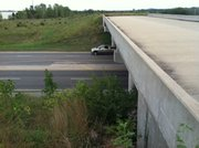 "This photo, taken Sunday, shows a view that looks east across the bridge with a car, below, heading north on Iowa Street. The supports holding the bridge up are rated in ""good"" condition by state inspectors. A bridge less than a mile to the west — one that actually carries trafficway traffic — has supports rated in ""very good"" condition."