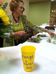 Susan McElwain, a trustee and member of the Lawrence Schools Foundation's Finance Committee, counts donations to a new fund established to help teachers buy school supplies for students who may need them as the school year continues. Attendees of the Community Education Breakfast initiated the fund by filling yellow cups on their tables Friday at the Holiday Inn Lawrence, 200 McDonald Drive.