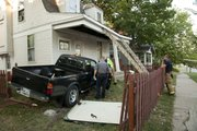 A pickup truck smashed through a fence and then into the front porch of a home in the 400 block of West Sixth Street Thursday evening.  According to witnesses, the eastbound truck crossed lanes, clipped a tree and then went airborne before crashing through the fence and into the porch. A truck tire was found in the front yard near the street. The homeowner was inside the front room reading to her child when the accident happened.