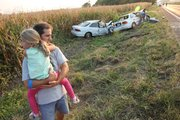 Jim Powers, Lawrence, holds his daughter Sarah, 4, after his wife, Marcia, and daughter swerved to avoid a head-on collision north of Lawrence. At least two people were injured — one critically — after a serious accident on U.S. Highway 24-40 near the Lawrence Municipal Airport. The accident was reported about 6:30 p.m. near mile marker 395 on the highway, between East 1500 and 1600 roads. Two people were transported by ambulance to area hospitals. Traffic was backed up in both directions Friday evening, with emergency personnel directing motorists through the area. Both vehicles involved in the accident, a white Honda and white Acura passenger vehicle, had come to rest in the ditch on the south side of the road. Additional information regarding the accident and condition of the patients was unavailable Friday night.