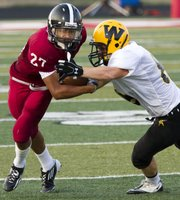 Lawrence High's Erick Mayo (27) tries to break free from Shawnee Mission West's Joel Spiller during Lawrence High's season opening football game against Shawnee Mission West Friday, Sept. 2, 2011 at Lawrence High.