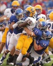 Kansas special teams players Keeston Terry, left, Ben Heeney (31) and Huldon Tharp (34) collapse on McNeese State returner Champlain Babin during the first quarter on Saturday, Sept. 3, 2011 at Kivisto Field.
