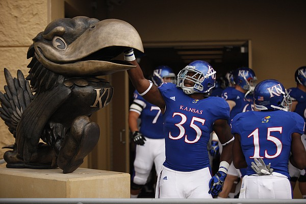 Kansas defensive end Toben Opurum reaches up to touch the recently installed bronze Jayhawk outside the Anderson Family Football Complex before kickoff against McNeese State on Saturday, Sept. 3, 2011 at Kivisto Field.