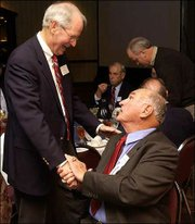 Former Kansas basketball coach Ted Owens, left, greets ex-KU player and coach Don Fambrough at a benefit dinner for the Bert Nash Center in this file photo from 2004. Fambrough died Saturday, Sept. 3, 2011 at 88.