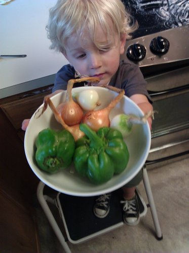 The kiddo displays our CSA onions and peppers before they were chopped up and spread on a pizza. The pizza&#39;s crust was made using a mixture of white flour and whole-wheat flour from our CSA, Rolling Prairie Farmers Alliance.