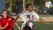 Lawrence High's Robert Lyan (10) tries to make a move for the ball against Blue Valley West on Tuesday at LHS.