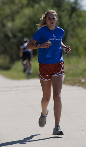 """Danielle Snider, a Kansas University graduate student from Fishers, Ind., jogs on the South Lawrence Trafficway multi-sport path Tuesday, during a 6-mile run. A former cross country runner with the Air Force Academy, Snider says she runs everyday and says the 10-mile paved path in west Lawrence is her favorite running trail. """"I love it,"""" she said."""