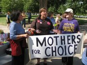 Women attending a rally Wednesday outside the Capitol hold a pro-choice sign. From left to right they are Carol Ramirez of Topeka, Melissa Carlson of Overland Park and Marilynn Ault of Topeka.