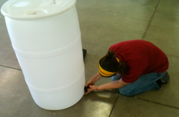 Shawna Trarbach, a storm water quality technician with the city of Lawrence, works on a rain barrel during a workshop this summer.