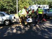 Personnel from Lawrence Douglas County Fire Medical, Lawrence police and the Kansas Highway Patrol attend to a person injured in an auto accident on Iowa Street, between Stratford Road and University Drive. The accident was Thursday morning, Sept. 9, 2011.