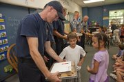 In conjunction with the 10th anniversary of 9/11, second-grade students at Quail Run School, 1130 Inverness Drive, handed out treat trays to firefighters from Station 3 on Friday as part of a salute to first responders from the area. Lincoln Smith, center, and Elizabeth Newman gave a tray of cookies to Mark Campbell.