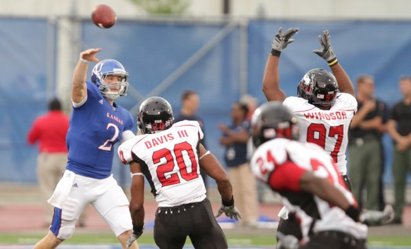 Kansas quarterback Jordan Webb throws over Northern Illinois defenders Tommy Davis and Joe Windsor during the first quarter on Saturday, Sept. 10, 2011 at Kivisto Field.