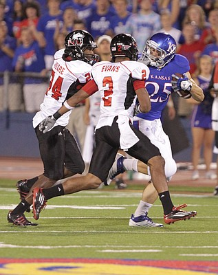 Kansas running back Brandon Bourbon gets twisted around by Northern Illinois cornerback Dominique Ware (24) during a run in the third quarter on Saturday, Sept. 10, 2011 at Kivisto Field. Also pictured is NIU cornerback Sean Evans.