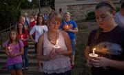 Kansas University sophomores Paige Kauffman, Littleton, Colo., center, and Julianne Melanson, Leavenworth, right, participate in a candlelight service commemorating the 10th anniversary of 9/11 at the Campanile on the KU campus on Sunday.