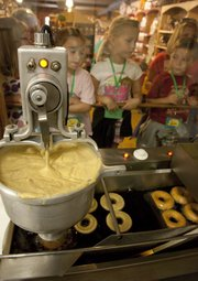 Doughnut rings drop into hot oil to fry at Louisburg Cider Mill. Visitors, like these kindergartners from Morse Elementary School in Overland Park, can watch the small production line through a window.