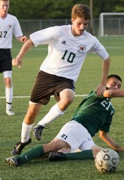 Free States Jake Walter (10) steps over Desoto player Alejandro Carlos tackle attempt Monday, Sept. 12, 2011 at Free State.