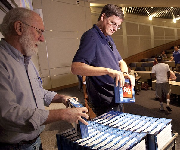 Google vice president of engineering, Brian McClendon, right, a Kansas University graduate who co-founded Google Earth, pulls a Motorola Xoom tablet from a cart as he hands it out as gifts to a class of engineering students. He's pictured with Gary Minden, KU professor of electrical engineering and computer science.