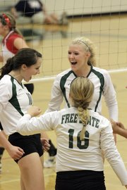 Shelby Holmes, from left, Molly Ryan and Kylie Dever (16) celebrate a point as Free State girls volleyball played Emporia in the first match of a triangular meet at home Tuesday, Sept. 13, 2011.