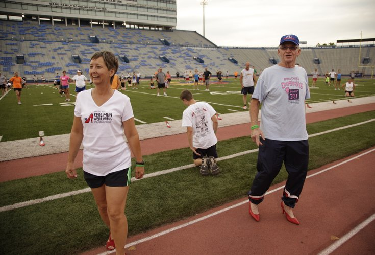 "Don ""Red Dog"" Gardner walks awkwardly in red heels with his wife, Beverly, for a portrait during a Dog Days workout on Tuesday, Sept. 13, 2011 at Memorial Stadium. The photo will be featured in the 2012 Red Shoe calendar, which features some recognizable male figures in Lawrence, wearing red heels and also benefits the Willow Domestic Violence Center."