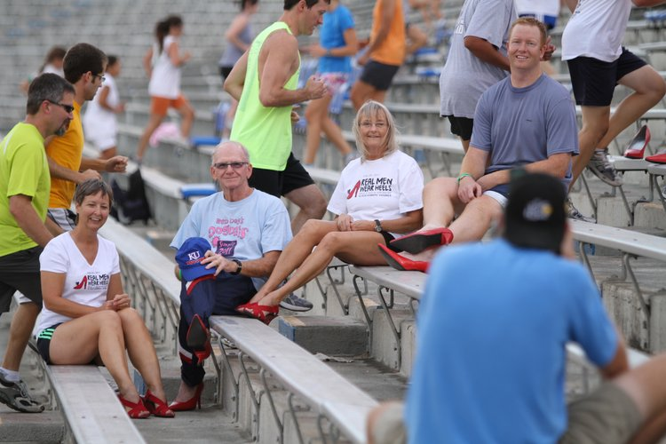 "Don ""Red Dog"" Gardner and his wife, Beverly, left, sit for a portrait in red heels with longtime Dog Days participants Ellen Young and Ryan Wedel, both of Lawrence, during a Dog Days workout on Tuesday, Sept. 13, 2011, at Memorial Stadium. The photo, shot by Earl Richardson, will be featured in the 2012 Red Shoe calendar, which features some prominent male figures in Lawrence wearing red heels and benefits the Willow Domestic Violence Center."