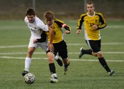 Free States Jake Walter, left, battles for the ball against Shawnee Mission West defenders. The Firebirds won, 2-1 in overtime, on Thursday at FSHS.