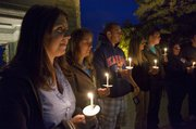A candlelight vigil for victims of sexual assault was organized Thursday evening at the Campanile on the KU campus.  Kansas student  Ashley Arenholz, from left,  Emily McGinnis and Anthony Ungaro hold candles with others during a momenbt of silence.  The gathering was part of Emily Taylor Women's Resource Center's awareness week.