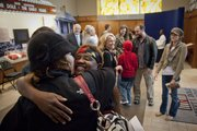 Newly naturalized citizen Stella Ayers, of edgerton, is congratulated with a hug and a kiss from her friend Beth Cockle, of Leawood, on Friday, Sept. 16, 2011, following a naturalization ceremony at the Dole Institute of Politics. Ayers, who is originally from Nigeria, was one of 99 individuals who were granted U.S. citizenship in the ceremony.