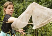 Eleven-year-old Savannah Beckerman, Kansas City, Mo., concentrates as she nets a monarch butterfly Sunday at the Prairie Park Nature Center, 2730 Harper St.