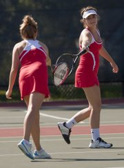Lawrence High School doubles partners Haley Ryan, left, and Abby Gillam bump rackets after winning a volley at the LHS quard tennis meet Monday, Sept. 19, 2011 at LHS.