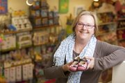 Kris Bailey, owner of Blue Dandelion, 841 Mass., is pictured with a pair of little girls shoes at her store. Bailey says that, while tempting, parents should avoid buying roomy shoes for new walkers. The extra room, while good for growing, can make it hard for new walkers to move properly.