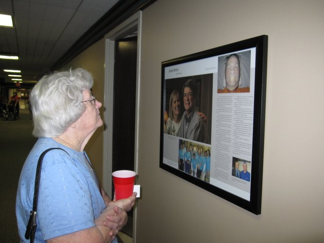 Doris Sullivant, Lawrence, stops to read one of many cancer stories that line the wall outside The Oncology Center at Lawrence Memorial Hospital on Tuesday, Sept. 20, 2011. Sullivant was one of the first oncology patients under the LMH program in 2000.