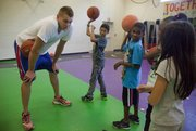 Former Kansas University basketball player and current member of the Oklahoma City Thunder Cole Aldrich helps tip off FitClub34, which encourages physical fitness among youth. He was at the Boys and Girls Club of East Heights in Lawrence on Tuesday, Sept. 20, 2011.