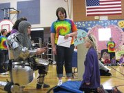 """Sir Julian,"" portrayed by Sam Lane, bestows New York School knighthood to third-grader Rose Morland, as teacher Amber Cook looks on. Rose was one of 10 students knighted during the school&squot;s Character Counts Assembly conducted Sept. 16, 2011, in the gymnasium at the school, 936 N.Y. The photographer: Olive Olsen, a fifth-grader at New York."