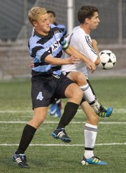 Lawrence High senior Zach Wustefeld, right, and Shawnee Mission East senior Jeremy Young fight for control of the ball during Lawrence High's soccer match against Shawnee Mission East Thursday, September 22, 2011 at LHS.