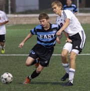 Shawnee Mission East's Hank Tamblyn, left, pushes past Lawrence High's Donald Harris as the two go after the ball during Lawrence High's soccer match against Shawnee Mission East Thursday, September 22, 2011 at LHS.