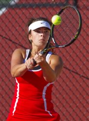 Abby Gillam gets a return on the ball in Lawrence High girls tennis doubles match play Thursday against Manhattan.