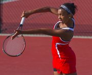 Taylor Eubanks  slams a return on the ball  in Lawrence High girls tennis doubles match play Thursday against Manhattan.