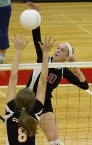 Lawrence High's Monica Howard (10) hits a spike past a Shawnee Mission Northwest blocker during Lawrence High's volleyball match against Shawnee Mission Northwest Thursday, September 22, 2011 at LHS.