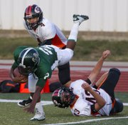 Free State running back Shawn Knighton tries to leap over Shawnee Mission Northwest linebacker Wade Drouillard's (43) tackle Friday, September 23, 2011 at FSHS.